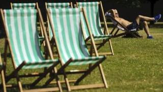 A man sunbathes in Hyde Park on August 18, 2012