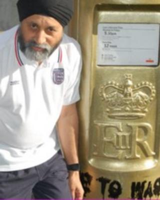 Sub postmaster Sardarah Singh next to the vandalised post box
