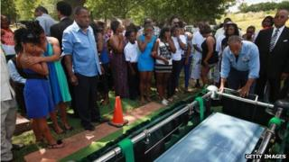 Mourners watch as the remains of Joseph Briggs is lowered into a grave at Oak Woods Cemetery on 20 June 2012 in Chicago, Illinois