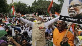 Indian protesters hold photographs of Indian Prime Minister Manmohan Singh as they shout slogans during an anti corruption protest near the Indian parliament in New Delhi, India, Sunday, Aug. 26, 2012