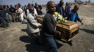 A group of men carry the coffin of a miner killed during the strike