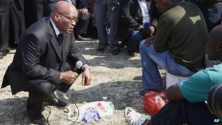 "South Africa""s President Jacob Zuma, left, interacts with striking mine workers at the Lonmin mine near Rustenburg, South Africa, Wednesday, Aug. 22, 2012."