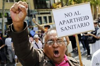 """An immigrant holds a banner reading """"No to the healthcare apartheid"""" in Madrid, 1 September"""