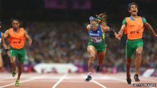 Terezinha Guilhermina of Brazil and guide Guilherme Soares de Santana cross the line to win gold in the Women's 100m T11 Final