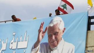 Worker places Lebanese flag on billboard depicting Pope Benedict XVI at airport road in Beirut. 13 Sept 2012