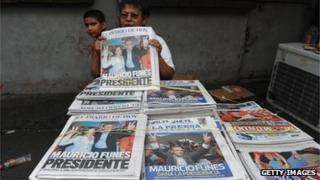 A woman sells newspapers in downtown of San Salvador
