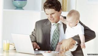 Man working at home, with a baby in his arms
