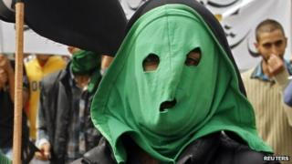 A masked protester supports a strike call in Kashmir against an anti-Islam film