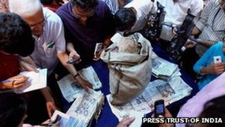 Journalists look at the newspapers taken out of the diplomatic bag