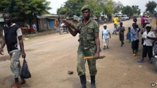 An M23 rebel walks the streets of the North Kivu town of Rubare near Rutshuru, 75km (48 miles) north of Goma, DR Congo