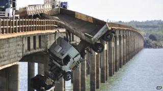 A truck hangs from the Chavantes bridge near Fartura, southern Brazil, Saturday, Sept. 22, 2012. The driver survived uninjured.