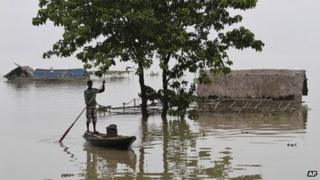 A man rows a country boat past partially submerged houses in Burhabrhi village about 65km (41 miles) east of Gauhati, Assam state, India, Monday, Sept. 24, 2012