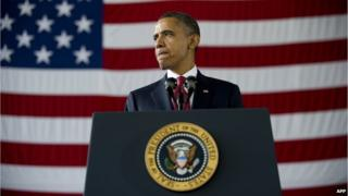President Obama standing at a lectern with the Stars and Stripes behind him
