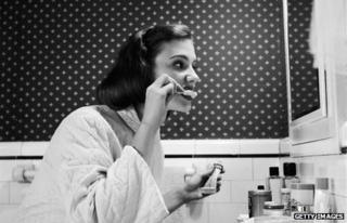 Young woman brushing her teeth in the 1930s