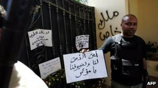 "A Libyan security guard holds a slogan, which reads in Arabic ""Where is the security for us and for our guests"" at the main entrance of the US consulate in Benghazi on 18 September 2012"