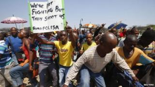 Striking platinum miners march near the Anglo-American Platinum mine near Rustenburg, South Africa, 5 October 2012
