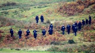 A police team search land near Machynlleth