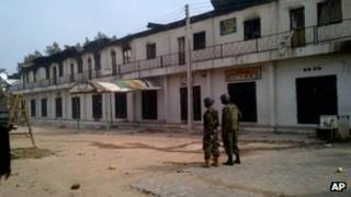 Soldiers stand near burnt shops in Maiduguri - 8 October