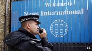 Policeman stands outside the headquarters of News International
