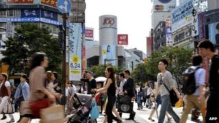 Pedestrians cross a road in front of the Shibuya station in Tokyo on 21 June, 2011
