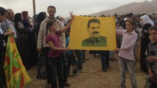PKK supporters hold up banner of imprisoned PKK leader Abdullah Ocalan
