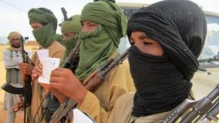 Young fighters, including 13-year-old Abdullahi, right, and 14-year-old Hamadi, second right, display their Quranic studies notes as their Islamist commanders look on, in Douentza, Mali, 27 September 2012