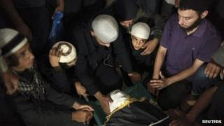 """The son of Salafi Islamist Hisham al-Saedni sits next to his father""""s body during his funeral at a mosque"""