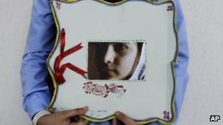 Pakistani student holds a picture of Malala Yousufzai during a tribute at the Pakistani Embassy in Abu Dhabi, Oct. 15, 2012.