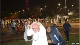 Protesters running from tear gas during a demonstration against proposed changes to election laws in Kuwait