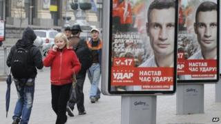 People walk past election posters of Ukrainian boxer and Chairman of the Ukrainian Udar Party, Vitali Klitschko in Kiev, Ukraine, Thursday, Oct. 18, 2012.
