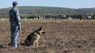 A prison officer watches over inmates as they harvest potatoes on the field of a penal colony in Russia. File photo