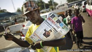 A man holding a newspaper, in Zimbabwe