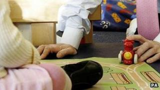 Man in shirt and tie playing with child's toys