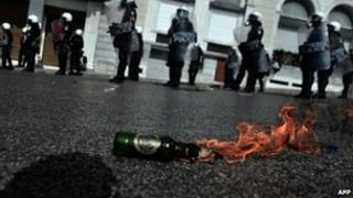 A petrol bomb burns on an Athens street during a protest against cuts, 18 October