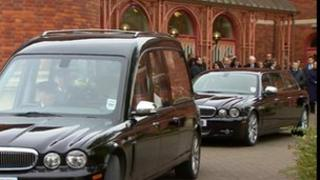 The hearse leaving the church