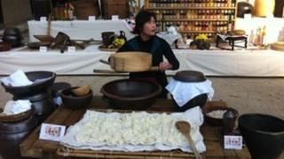 A woman demonstrating South Korean rice making technique