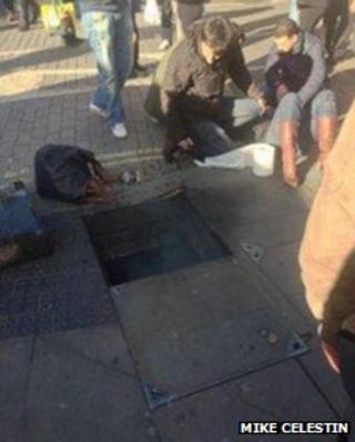 The woman lies injured as smoke emerges from the manhole