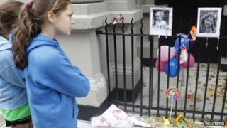 A young girl looks at a makeshift memorial left outside the Krim family apartment in New York