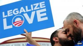 Two men campaigning in favour of same-sex marriage kiss in front of a Legalize Love placard