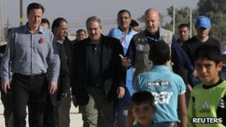 David Cameron walks with Jordanian Foreign Minister Nasser Judeh and United Nations High Commissioner for Refugees representative to Jordan Andrew Harper