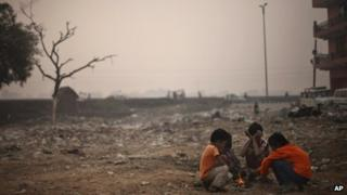 Indian boys sit around a small fire as the morning sun is enveloped by a blanket of smog, caused by a mixture of pollution and fog in New Delhi, India, Wednesday, Nov. 7, 2012