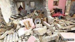 A Palestinian woman surveys damage from an Israeli air strike in Rafah, 11 Nov