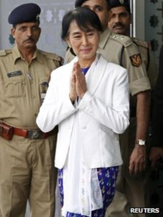 """yanmar""""s opposition leader Aung San Suu Kyi makes a gesture of greeting upon her arrival at the Indira Gandhi international airport in New Delhi November 13, 2012."""