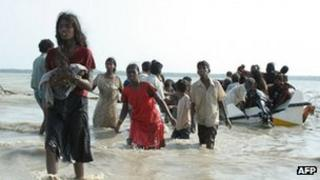 A Tamil mother holding her baby walks ashore after fleeing the conflict in 2009 by boat
