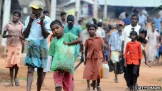 Internally displaced Tamils leave their camp with belongings in the northern town of Vavuniya (23 December 2009)