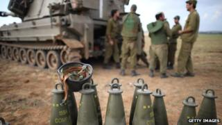 Israeli soldiers prepare an artillery emplacement overlooking Gaza on Israel's border with the Gaza Strip