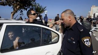 Israeli police officers detain a man who allegedly attacked a security guard at the US embassy in Tel Aviv