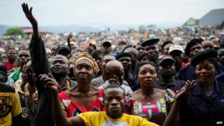 Residents of Goma react as they listen to M23 rebel group spokesman at a stadium in Goma, 21 November 2012
