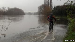 Cyclist riding through water on the River Thames tow path in Reading