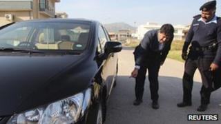 Senior journalist for the Geo News television station Hamid Mir points to his car where a bomb was found underneath, in Islamabad November 26, 2012.